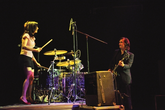 Drummer Giovanna Pizzorno playing with standing up in red high heels with bass player Laurent Lanouzière