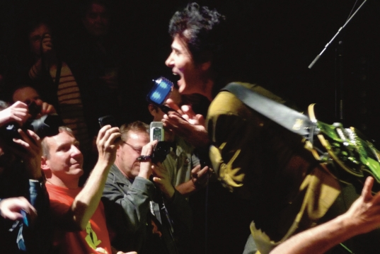 Shot of Tav Falco in gold suit singing and leaning over the audience members, whose hands are full of cameras and smartphone