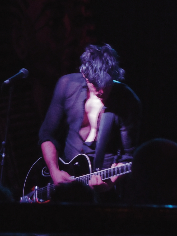 Guitarist Peter Mavrogeorgis caught in motion looking down with shirt open