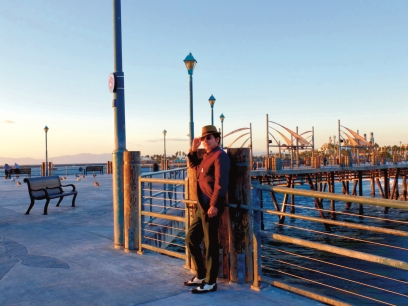 Musician Tav Falco in colorful suit and a hat stands on Redondo pier in the late even sun
