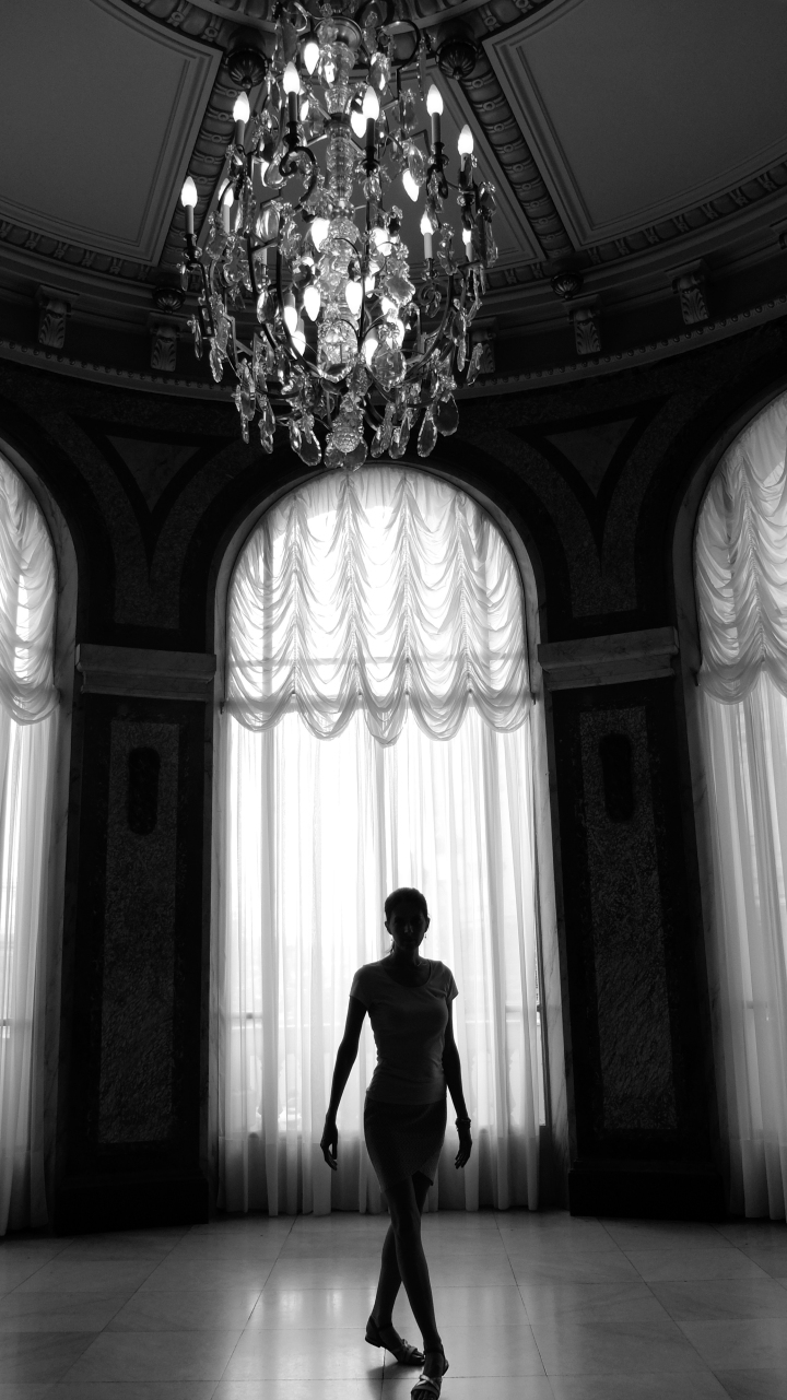 Stunning black and white image of the silhouette of a graceful dancer in the Casino Monte Carlo with chandelier