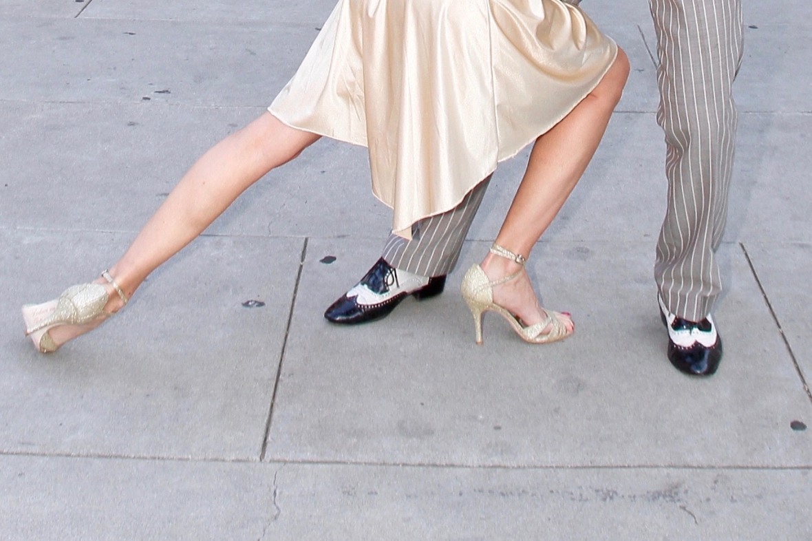 The beautiful legs and shoes of a woman in a gold dress and shoes dancing tango witha man in a grey and white striped suit