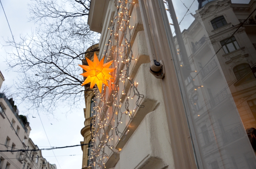 A bright orange star-shaped light hands with cascading soft Christmas lights against the stark winter trees and sky