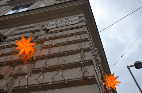 The bright orange star lights contrast sharply with the muted colors of a Vienna winter