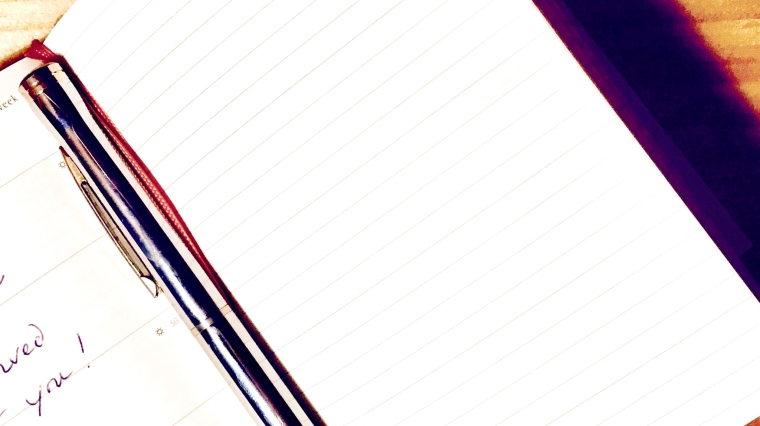 Closeup of an open notebook with a blank white page ready to be written in