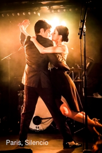 A couple stopped in a dramatic tango pose framed by a bright golden light