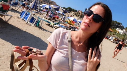 Via Estela standing on a sunny beach in Mallorca carrying stones washed ashore