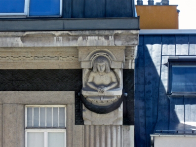 A stone carved woman's upper body among blue roof tiles in Vienna.