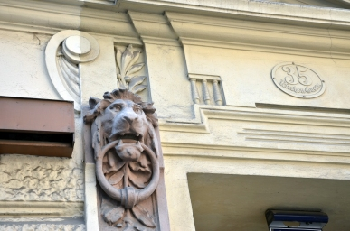 Ornate entrance details with lion head and organic flourishes.