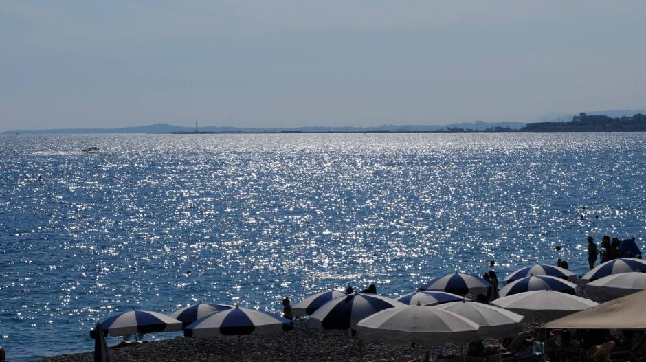 A boat glides across the glistening blue water off the coast of Nice.