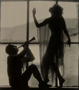 Beautiful photo of the silhouettes of a horn player and a dancer in front of a large window