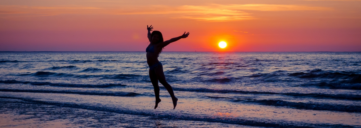 Women jumping on a beach in front of a beautiful sunset.