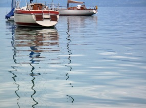 Sailboats reflected on the fresh water of an Alpine lake